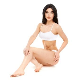 Fitness young woman with a beautiful body sitting on white background