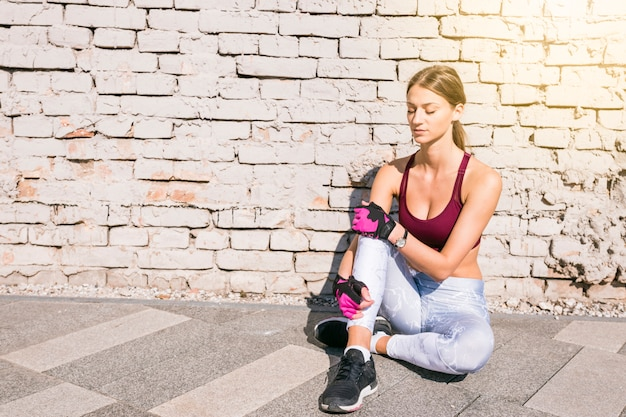 Fitness young woman with closed eyes sitting against brick wall