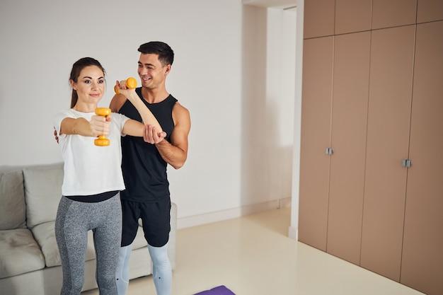 一緒に家のトレーニングをしているフィットネスに敏感な笑顔のカップル