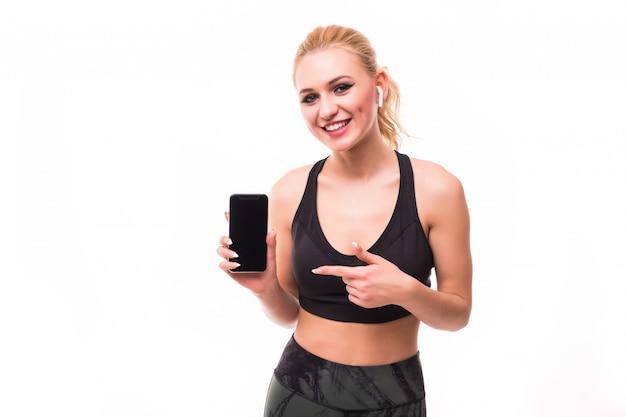 Fitnessgirlは白の前で真新しいスマートフォンを示しています
