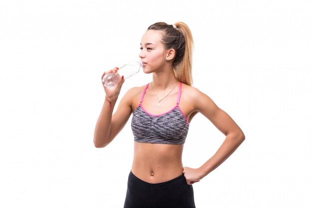Fitnesswoman drinking water from a transperent bottle on a white
