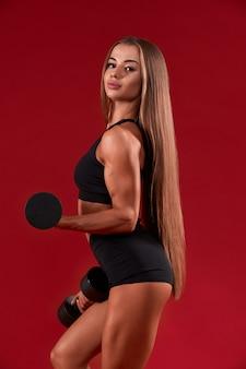 Фитнес-женщина позирует с гантелями, изолированными на красном