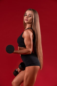 Fitnesswoman posing with dumbbells, isolated on red