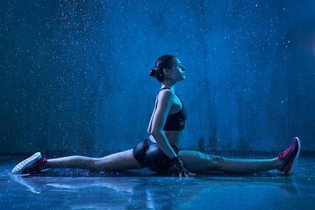 雨の下でスプリットを練習しているフィットネスウーマン
