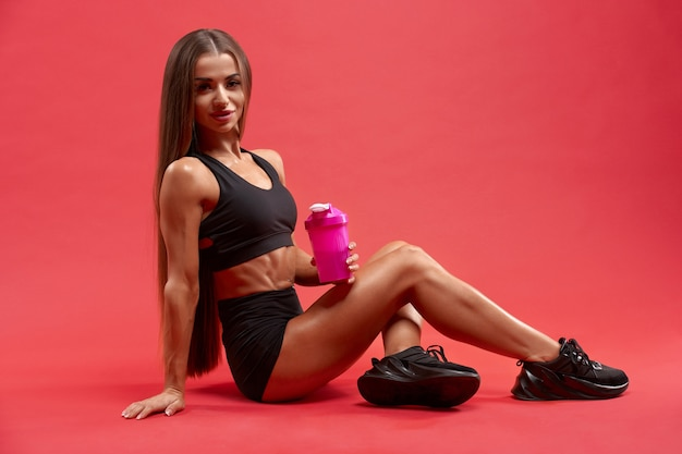Fitnesswoman seduto con shaker sul pavimento dello studio