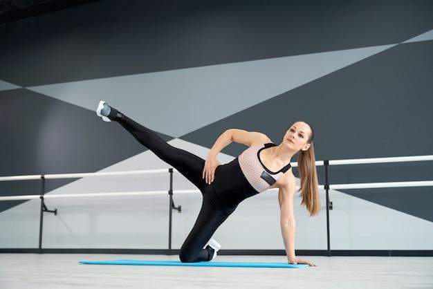 Fitnesswoman training on mat in hall