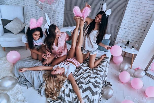 彼女にぴったりです。ガールフレンドの足にバニーの耳をつけようとし、ベッドに座って笑っている遊び心のある若い女性の上面図