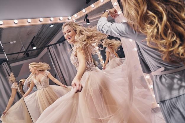 딱 맞습니다. 그녀의 여자 친구가 피팅 룸에서 그녀의 웨딩 드레스를 조정하는 동안 웃는 매력적인 젊은 여자
