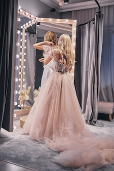완벽하게 맞습니다. 피팅 룸에 서 있는 동안 그녀의 여자 친구에 드레스를 조정 하는 젊은 여자의 전체 길이 후면 보기