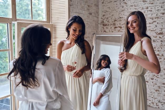 완벽하게 맞습니다. 피팅 룸에서 신부를 보면서 웃는 두 매력적인 젊은 여성