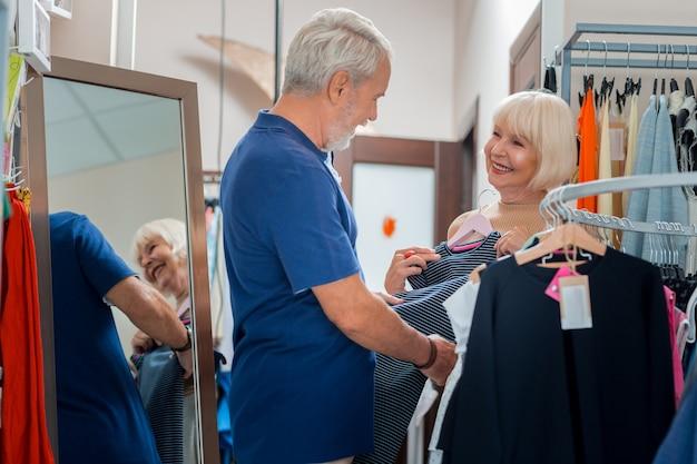 あなたにぴったりです。ショッピングストアで彼女の前に立っている間、彼の女性のドレスを賞賛して見ている喜んでいる白髪の夫