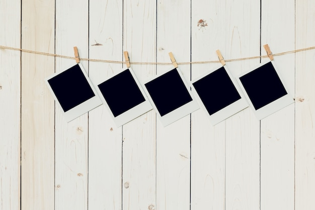 Five (5)blank photo frame hanging on white wood background with space.