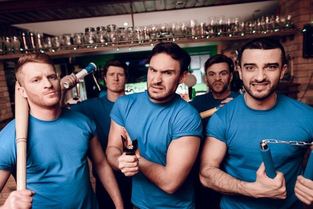 Five aggressive sports fans hooligans at bar