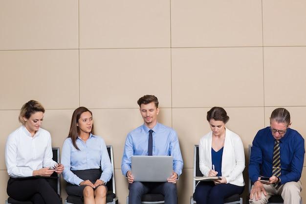 줄에 앉아있는 빈 포스트를위한 5 명의 지원자