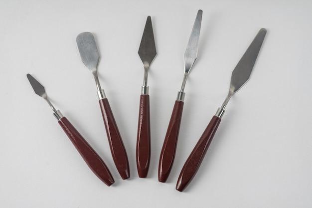 5つのアートパレットナイフが白いアートキャンバスにあります