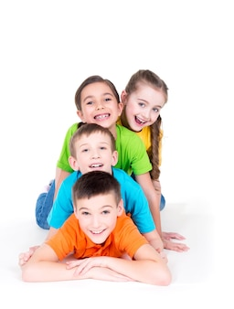 明るくカラフルなtシャツで床に横たわっている5人の美しい笑顔の子供たち-白で隔離。