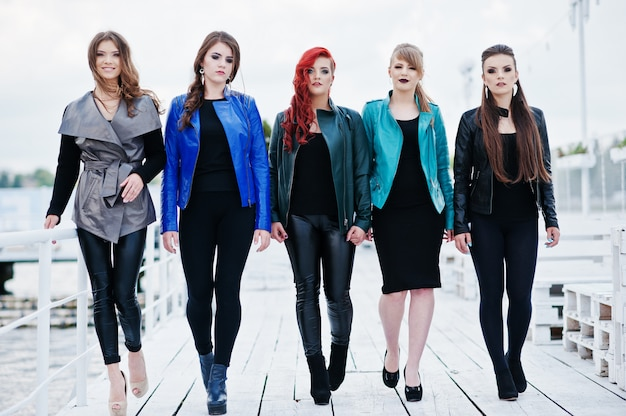 Five beautiful young girls models at leather jackets posing on pier
