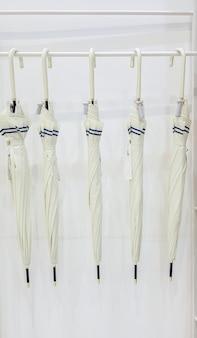 베이지색 우산 5개가 흰색 배경에 있는 옷걸이에 걸려 있습니다. 장마철을 대비하고 있습니다. 흰색 옷걸이에 걸려 있는 선반에 5개의 현대적인 우산이 있습니다.