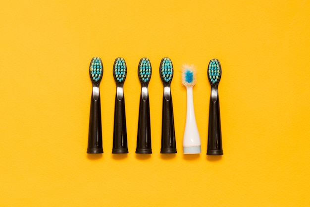Five black new toothbrushes and one old white toothbrush on a yellow background
