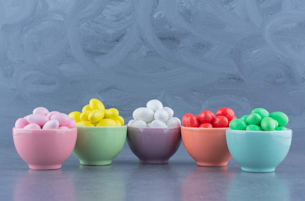 Five bowls of gum, on the marble surface