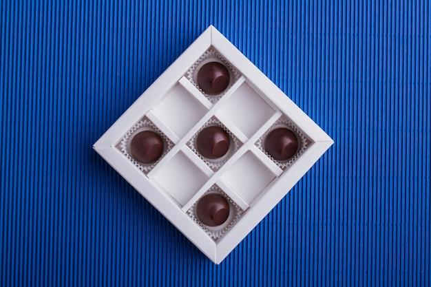Пять коричневых шоколадных конфет в коробке на синем фоне
