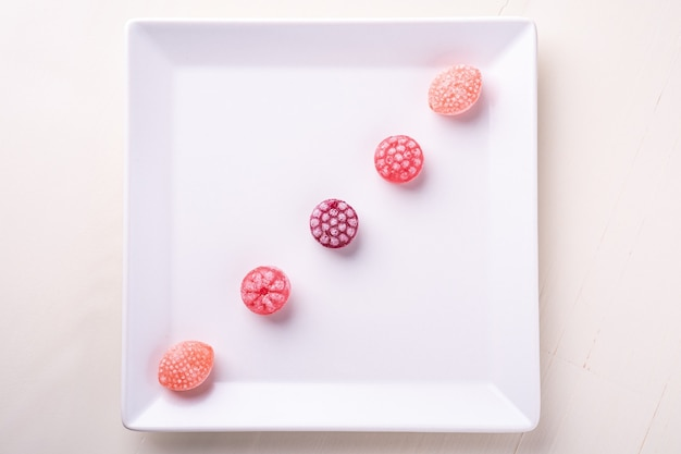 Five candy canes sweets in form of juicy berries on white plate on white background isolated, top view