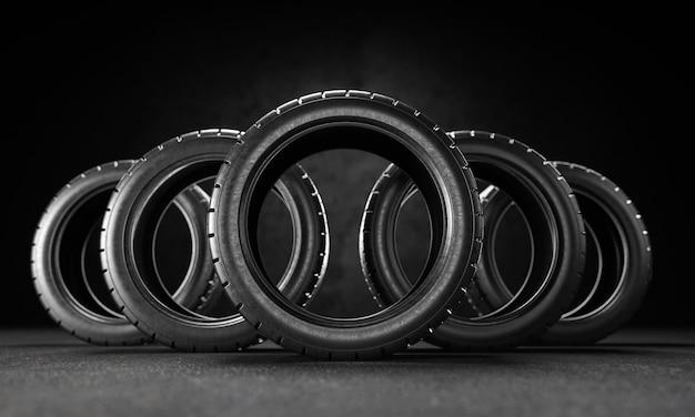黒の背景のアスファルトに5つの車のタイヤ。 3dレンダリング