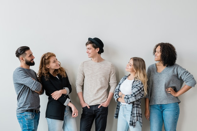 Five casual carefree guys and girls having friendly talk at leisure while standing against white wall in studio