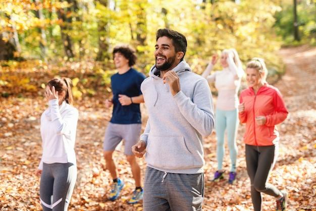 秋の森で実行されているスポーツウェアの5人の陽気なランナーフィットネスの性質の概念。側面図。