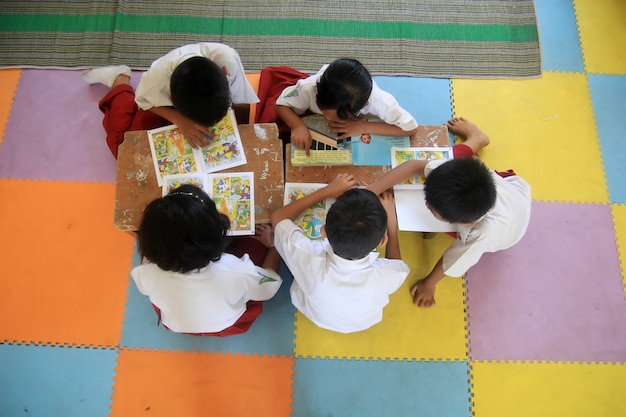 Five children of elementary school students are reading comic books stories in the school library.