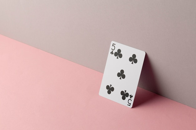 Five of clubs on pink background
