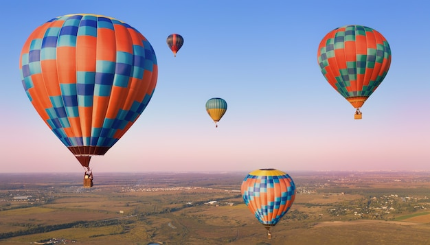 Five colorful balloons in the air over the plains.
