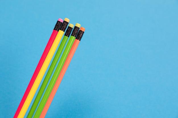 消しゴムで5つのカラフルな鉛筆が分離された紺onに横たわっています。