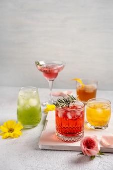 白いテーブルの上のグラスで5つのカラフルな夏のカクテル。新鮮な夏の飲み物の品揃え。