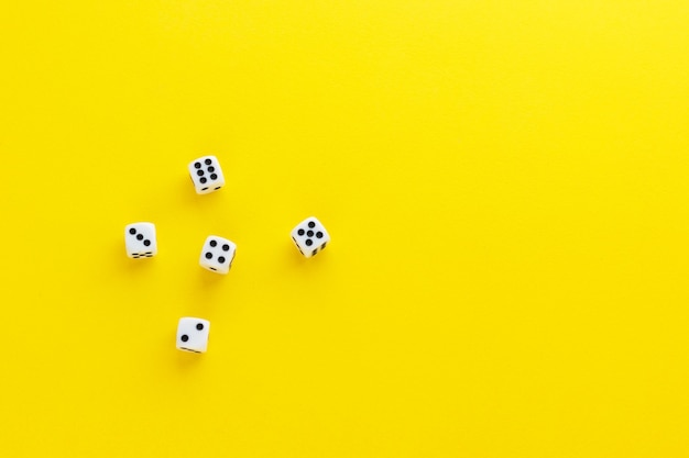 Five dice showing different sides on yellow background. playing cube with numbers. items for board games. flat lay, top view with copy space.