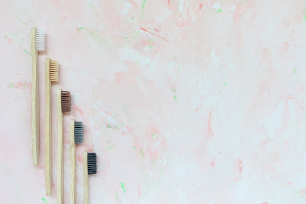 Five different natural wooden bamboo toothbrushes. plastic free and zero waste concept. top view, pink backgroundon, copy space