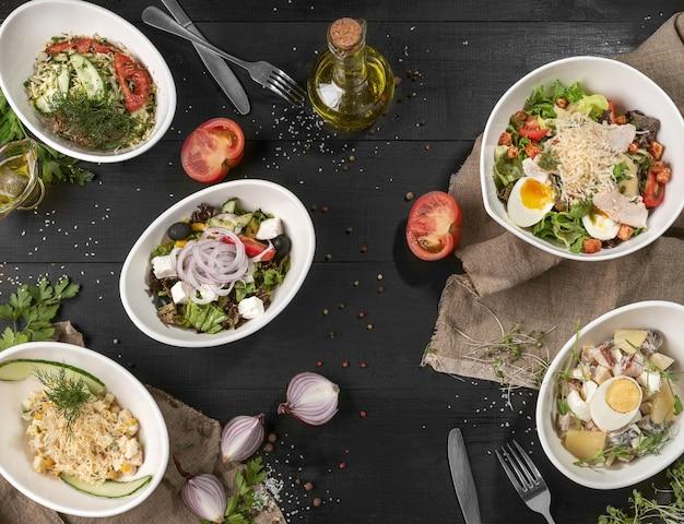 Пять разных салатов на черном деревянном столе