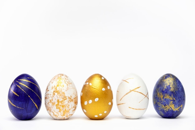 Five easter eggs colored blue, white and golden on white