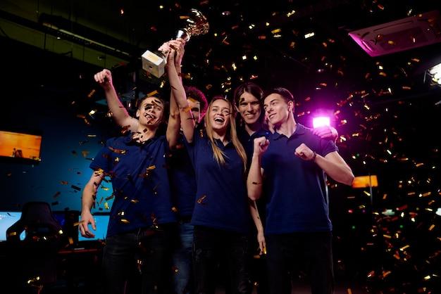 落ちてくる紙吹雪に立っている間、サイバースポーツの競争で勝ったことの誇りを表現する5人の恍惚とした若いフレンドリーなビデオゲーマー