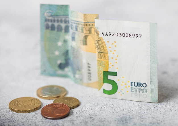 Five euro banknote with coins