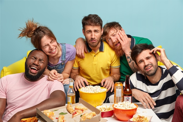 Five fellows laugh loudly as watch funny comedy movie or comic show