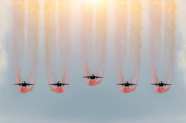 Five fighter jets fly together with red smoke.