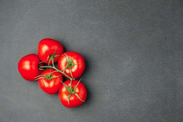 Five fresh tomatoes on dark wooden surface, top view.