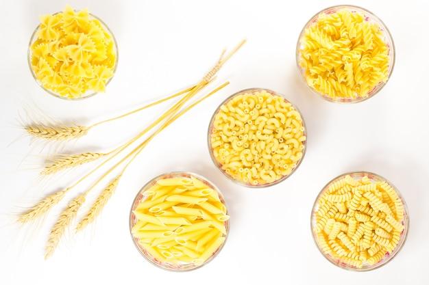 5杯のパスタ。小麦の穂。白色の背景。上面図