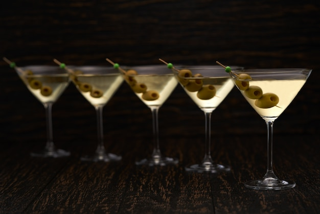 Five glasses of alcoholic beverage on a black table