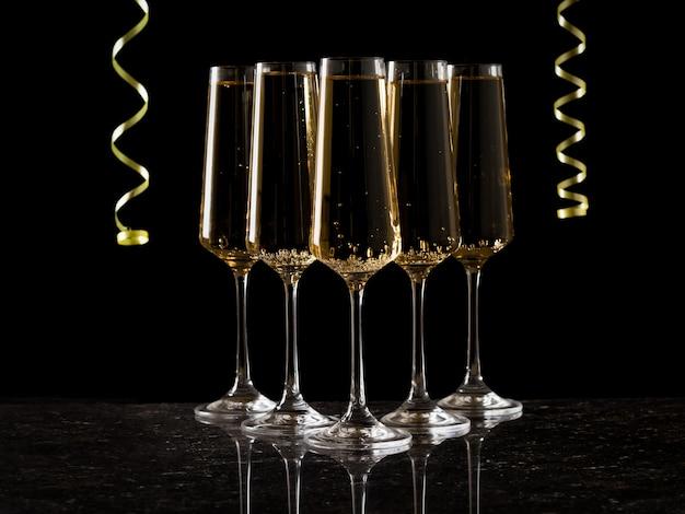 Пять бокалов игристого вина и желтый серпантин