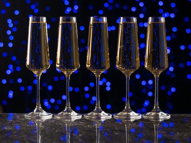 블루 bokeh에 대해 테이블에 깔끔하게 서있는 와인 5 잔