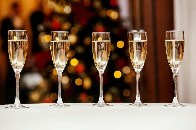 Пять бокалов с крутым вкусным шампанским или белым вином на кейтеринге.