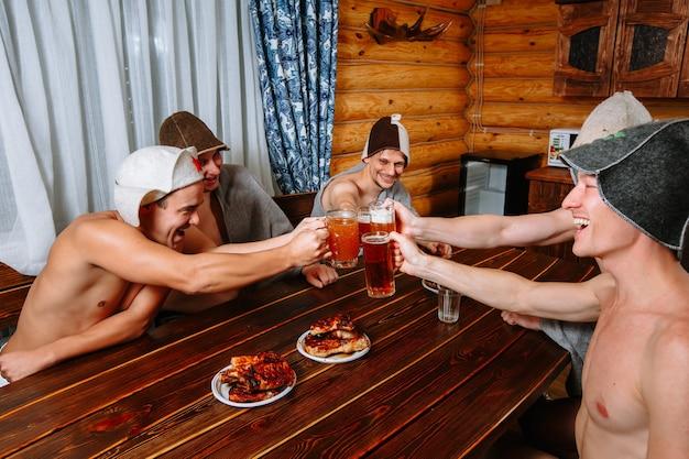Пятеро парней расслабляются в сауне после парилки и пьют пиво