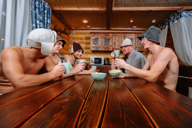 スチームルームの後、5人の男がサウナでリラックスしてお茶を飲みます